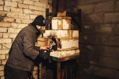El herrero barbudo enciende un fuego en el horno foto de archivo libre de regalías