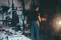 El herrero calienta el artículo antes de forjar foto de archivo