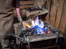 El herrero calienta el hierro en el fuego del horno foto de archivo libre de regalías