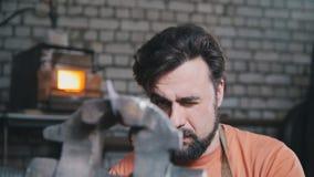 El herrero dobla el cuchillo del metal con queja en la fragua del taller, retrato Fotos de archivo