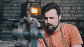El herrero dobla el cuchillo del metal con queja en la fragua del taller, retrato Imagenes de archivo