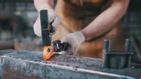 El herrero dobla la barra de hierro en el yunque con el martillo, trabajo del metal, cierre para arriba imágenes de archivo libres de regalías
