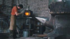 El herrero en fragua cerca del horno Fotos de archivo