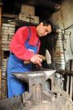 El herrero forja el hierro en el yunque Fotografía de archivo libre de regalías