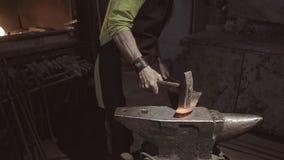 El herrero forja ferozmente un objeto candente que miente en un yunque Le da la forma de una cuchilla almacen de metraje de vídeo