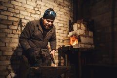 El herrero forja un de fundición en el yunque con un martillo foto de archivo