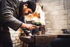 El herrero hace una forja artística de fundición en el yunque foto de archivo