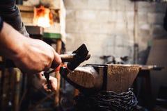 El herrero hace una forja artística de fundición en el yunque fotos de archivo