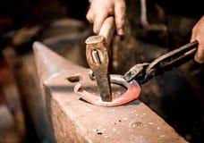 El herrero hace una herradura Fotos de archivo