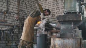 El herrero modera manualmente el cuchillo de acero en aceite de motor fotos de archivo
