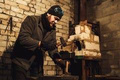 El herrero parte la leña para encender el horno fotografía de archivo libre de regalías