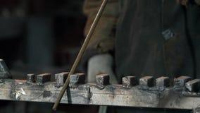 El herrero In Protective Clothing endereza barras de hierro almacen de video