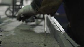 El herrero In Protective Clothing pone barras de hierro en la tabla almacen de video