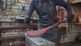 El herrero que forja manualmente en la herrería fotos de archivo