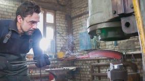 El herrero que forja manualmente en la herrería imagen de archivo libre de regalías