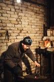 El herrero que forja manualmente el metal candente en el yunque foto de archivo libre de regalías