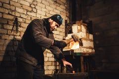El herrero que forja manualmente el metal candente en el yunque foto de archivo
