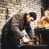 El herrero que forja manualmente el metal candente en el yunque imagenes de archivo