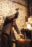 El herrero que forja manualmente el metal candente en el yunque y que vuela chispas fotos de archivo