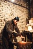El herrero que forja manualmente el metal candente en el yunque y que vuela chispas imagenes de archivo