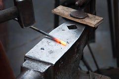 El herrero que forja manualmente el metal fundido en el yunque en herrería imagen de archivo libre de regalías