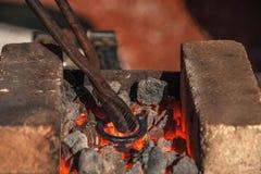 El herrero sostiene las pinzas y calienta el billete del hierro mientras que el hierro crea caliente una herradura en el yunque foto de archivo libre de regalías
