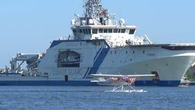 El hidroavión se desliza a lo largo de las ondas contra el contexto de los barcos de mar almacen de metraje de vídeo