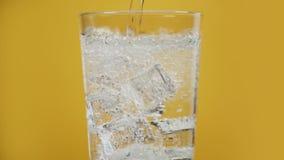 El hielo frío lleno de cristal de colada de agua chispeante de la bebida efervescente trasparent cubica amarillo almacen de video