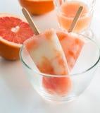 El hielo hecho en casa del yogur hace estallar con el jugo de pomelo fresco Imagen de archivo libre de regalías
