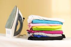El hierro se coloca con las pilas de lino coloreado planchado Pila de ropa imagenes de archivo