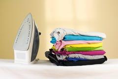 El hierro se coloca con las pilas de lino coloreado planchado Pila de ropa foto de archivo