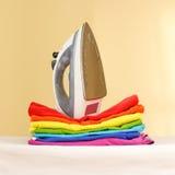 El hierro se coloca con las pilas de lino coloreado planchado Pila de ropa fotografía de archivo