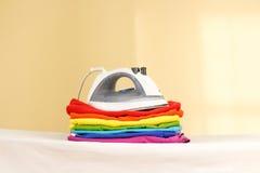 El hierro se coloca con las pilas de lino coloreado planchado Pila de ropa fotos de archivo