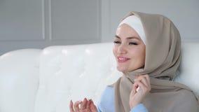 El hijab que lleva de la mujer musulmán joven feliz está bailando la sentada en el sofá y la música tradicional que escucha metrajes