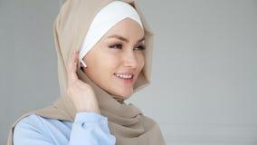 El hijab que lleva de la mujer musulm?n est? poniendo el auricular inal?mbrico en su o?do y tel?fono de discurso usando las auric metrajes