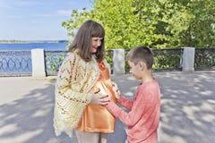 El hijo abraza el estómago de su madre embarazada Fotos de archivo libres de regalías