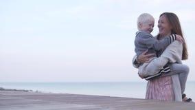 El hijo abraza a la mamá en la playa por el mar almacen de metraje de vídeo