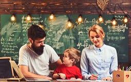 El hijo con la madre y el padre se sientan en el escritorio Pintura de la familia en plumas del fieltro en el papel Poco pintura  imágenes de archivo libres de regalías