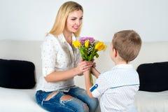 El hijo da a su madre querida un ramo hermoso de tulipanes Foto de archivo libre de regalías