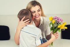El hijo da a su madre querida un ramo hermoso de tulipanes Imagenes de archivo
