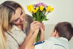 El hijo da a su madre querida un ramo hermoso de tulipanes Fotografía de archivo