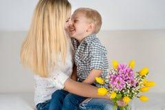 El hijo da a su madre querida un ramo hermoso de tulipanes Fotos de archivo libres de regalías