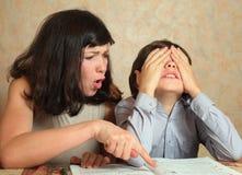 El hijo de la ayuda de la mamá hace la preparación difícil fotografía de archivo