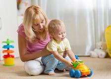 El hijo de la madre y del niño juega con el coche del juguete en cuarto de niños Fotografía de archivo