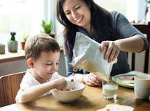 El hijo de la mamá pasa día de fiesta del tiempo que come el desayuno imágenes de archivo libres de regalías