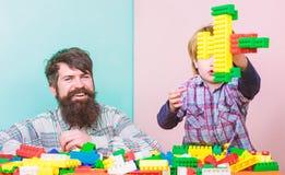 El hijo del padre crea construcciones Juego del padre y del muchacho junto Pap? y ni?o construir bloques pl?sticos Demostraci?n d fotografía de archivo libre de regalías