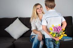El hijo guarda detrás de un ramo de tulipanes para una madre querida Foto de archivo