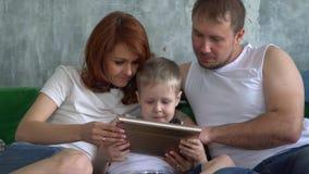 El hijo juega la tableta que se sienta en un sofá con los padres almacen de video