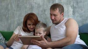 El hijo juega la tableta que se sienta en un sofá con los padres Gente joven con tecnología almacen de video