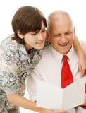 El hijo lee la tarjeta de felicitación al papá fotos de archivo
